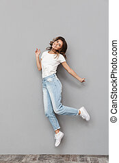 Full length portrait of a happy young woman jumping