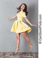 Full length portrait of a lovely girl in dress jumping