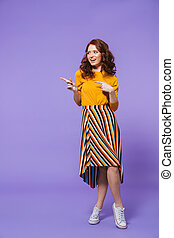 Full length portrait of a pretty young redheaded woman isolated over violet background, pointing finger at copy space