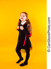 Full length portrait of a schoolgirl standing on yellow background