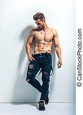 Full length portrait of a sexy muscular shirtless man posing...