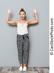 Full length portrait of a shocked woman showing her palms