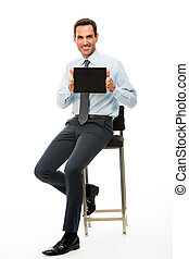 Full length portrait of a sitted businessman with digital tablet