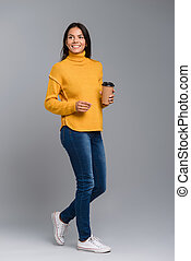 Full length portrait of a smiling casual young woman