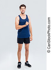 Full length portrait of a smiling man showing his biceps