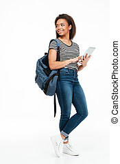 Full length portrait of a smiling teenage girl wearing backpack