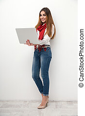 Full length portrait of a smiling woman with laptop