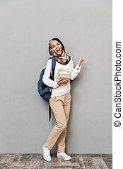 Full length portrait of a smiling young arabian woman