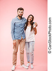 Full length portrait of a smiling young couple hugging
