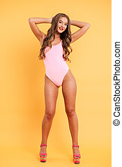 Full length portrait of a smiling young woman in swimsuit