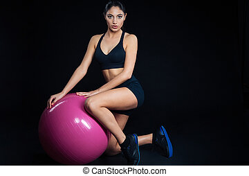 Full length portrait of a sports woman with fitness ball
