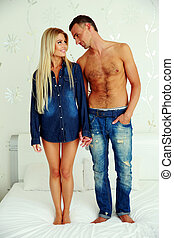 Full length portrait of a young couple standing on the bed and looking on each other