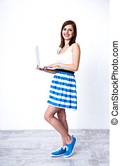 Full length portrait of a young happy woman standing with laptop