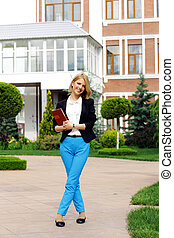 Full-length portrait of a young happy woman with tablet computer