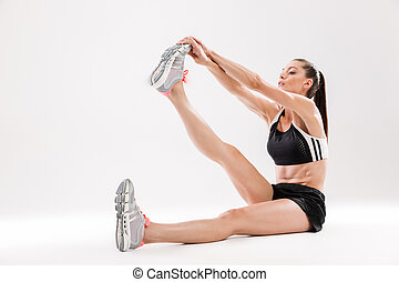Full length portrait of a young slim sportwoman stretching...