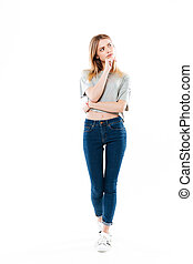 Full length portrait of a young thoughtful woman looking...