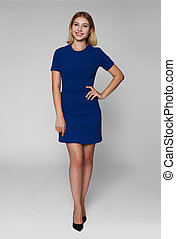 full length portrait of a young woman in blue dress