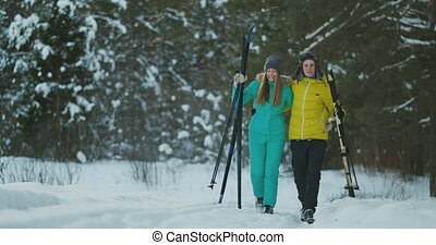Full length portrait of active young couple enjoying skiing in snowy winter forest, focus on smiling woman in front, copy space