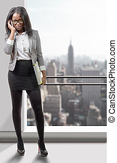 Full length portrait of an african american business woman smiling on phone