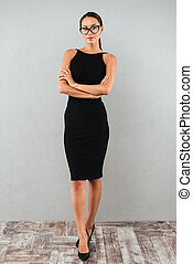 Full length portrait of an attractive businesswoman in black dress