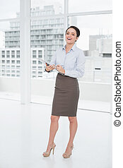 Full length portrait of an elegant young businesswoman with clipboard in a bright office