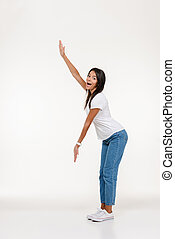 Full length portrait of an excited casual woman standing