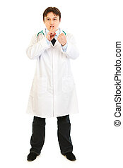 Full length portrait  of angry  medical doctor with finger at mouth and threaten with fist isolated on white