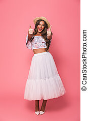 Full length portrait of beautiful excited woman 20s wearing straw hat and fluffy skirt showing thumbs up, isolated over pink background in studio