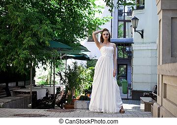 Full length portrait of beautiful model woman in white dress