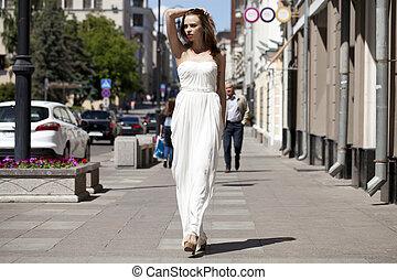 Full length portrait of beautiful model woman walking in white dress