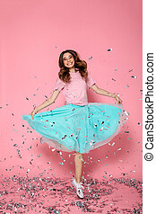 Full length portrait of beautiful cheerful woman posing with her skirt