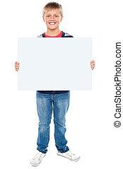 Full length portrait of boy holding blank whiteboard