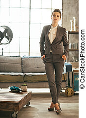 Full length portrait of business woman in loft apartment