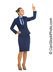 Full length portrait of business woman pointing up on copy space