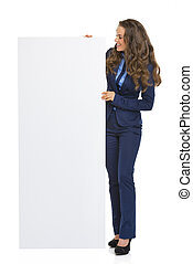 Full length portrait of business woman showing blank billboard