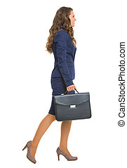 Full length portrait of business woman with briefcase going sideways