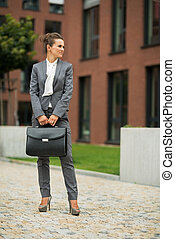 Full length portrait of business woman with briefcase in front o