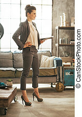 Full length portrait of business woman with magazine standing in