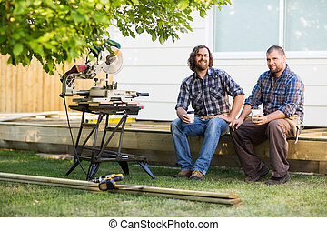 Full length portrait of carpenters holding disposable cups while sitting on wooden frame