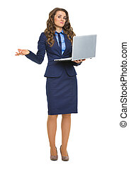 Full length portrait of clueless business woman with laptop shrugging shoulders