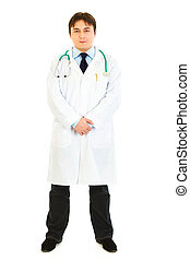 Full length portrait of confident medical doctor in uniform with stethoscope isolated on white