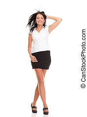 Full length portrait of confident young woman standing with hands folded on white background
