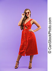 Full length portrait of content pretty woman 20s wearing red dress smiling at camera, standing isolated over violet background