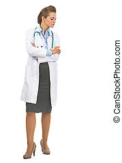 Full length portrait of doctor woman looking down on copy space