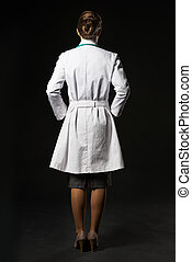 Full length portrait of doctor woman isolated on black. rear view