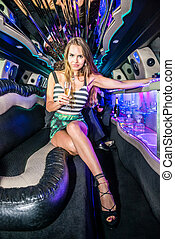 Full length portrait of elegant young woman holding champagne flute in limousine