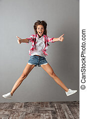 Full-length portrait of emotional jumping girl in casual wear, showing thumb up gesture,