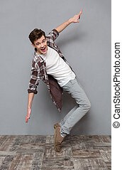 Full length portrait of excited dancing young man