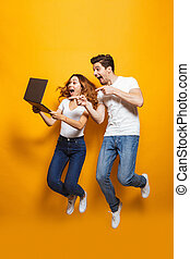 Full length portrait of excited man and woman jumping and using black laptop, isolated over yellow background