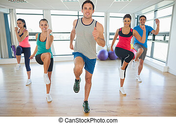 Full length portrait of fitness class and instructor doing pilates exercise in bright room
